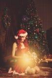 Νέα όμορφη χαμογελώντας γυναίκα santa κοντά στο χριστουγεννιάτικο δέντρο με Στοκ Εικόνα