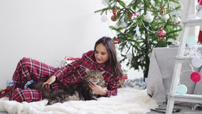 Νέα όμορφη χαρούμενη γυναίκα που βρίσκεται εκτός από fir-tree Χριστουγέννων σε ένα παιχνίδι κουβερτών με τη γάτα του Μαίην Coon κ φιλμ μικρού μήκους
