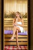 Νέα όμορφη χαλάρωση γυναικών στη σάουνα που τυλίγεται στην πετσέτα Στοκ φωτογραφία με δικαίωμα ελεύθερης χρήσης