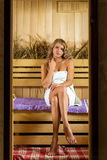 Νέα όμορφη χαλάρωση γυναικών στη σάουνα που τυλίγεται στην πετσέτα Στοκ Φωτογραφία