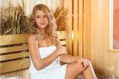 Νέα όμορφη χαλάρωση γυναικών στη σάουνα που τυλίγεται στην πετσέτα Στοκ Εικόνα