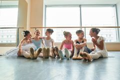 Νέα ballerinas που κάθονται στο πάτωμα και το αγκάλιασμα Στοκ Φωτογραφίες