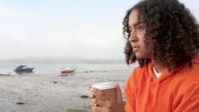 Νέα biracial γυναίκα που φορά το πορτοκάλι hoodie, τον εξαγωγέα καφέ κατανάλωσης από ένα λιμάνι που φαίνεται λυπημένο ή στοχαστικ απόθεμα βίντεο