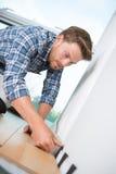 Νέα handyman κάμψη κάτω στο ξύλινο πάτωμα στοκ φωτογραφία με δικαίωμα ελεύθερης χρήσης