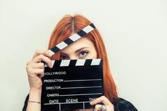 Νέα redhead γυναίκα με clapper τον πίνακα Στοκ Φωτογραφία