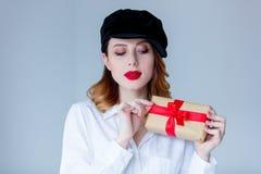 Νέα redhead γυναίκα στο κιβώτιο δώρων Χριστουγέννων εκμετάλλευσης καπέλων Στοκ Φωτογραφία