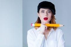 Νέα redhead γυναίκα στο μολύβι εκμετάλλευσης καπέλων chuge Στοκ φωτογραφίες με δικαίωμα ελεύθερης χρήσης