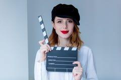 Νέα redhead γυναίκα clapboard κινηματογράφων εκμετάλλευσης καπέλων Στοκ εικόνα με δικαίωμα ελεύθερης χρήσης