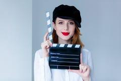 Νέα redhead γυναίκα clapboard κινηματογράφων εκμετάλλευσης καπέλων Στοκ Εικόνες
