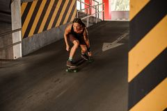 Νέα redhead οδήγηση τύπων κάτω από την άνοδο σε ένα longboard Στοκ φωτογραφία με δικαίωμα ελεύθερης χρήσης