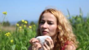 Νέα sneezes γυναικών από τα αυστηρά wildflowers αλλεργιών Αλλεργία και προβλήματα υγείας για τη νέα γυναίκα απόθεμα βίντεο