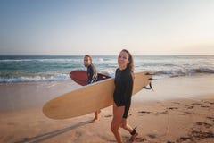Νέα surfers χαμόγελου ζευγών ευτυχή στην ωκεάνια ακτή, έννοια ταξιδιού διακοπών αθλητικού ενεργός τρόπου ζωής στοκ εικόνες