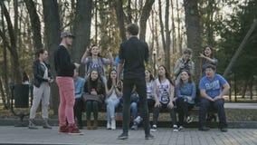 Νέα teens που παίζουν τους συλλαβόγριφους στο πάρκο άνοιξη με τους φίλους στο σούρουπο απόθεμα βίντεο
