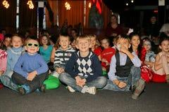 Νέα theatergoers τα παιδιά που προσέχουν ενθουσιωδώς τη μαριονέτα Χριστουγέννων των παιδιών παρουσιάζουν θέατρο Smeshariki Στοκ εικόνες με δικαίωμα ελεύθερης χρήσης