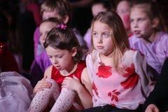 Νέα theatergoers τα παιδιά που προσέχουν ενθουσιωδώς τη μαριονέτα Χριστουγέννων των παιδιών παρουσιάζουν θέατρο Smeshariki Στοκ Φωτογραφία