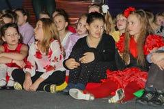 Νέα theatergoers τα παιδιά που προσέχουν ενθουσιωδώς τη μαριονέτα Χριστουγέννων των παιδιών παρουσιάζουν θέατρο Smeshariki Στοκ φωτογραφίες με δικαίωμα ελεύθερης χρήσης