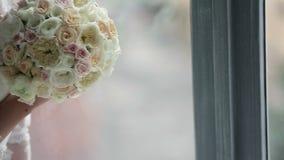 Νέα unrecognizable νύφη με τα λουλούδια κοντά στο παράθυρο φιλμ μικρού μήκους