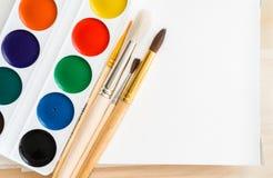 Νέα watercolors, καθαρές βούρτσες και ένα κενό λεύκωμα Στοκ Εικόνες