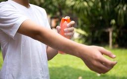 Νέες απωθητικές ουσίες εντόμων αγοριών ψεκάζοντας στο δέρμα με το μπουκάλι ψεκασμού Στοκ Εικόνες