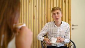 Νέες αρσενικές και γυναίκες σπουδαστές που έχουν το τσάι και τον καφέ κατανάλωσης συνομιλίας στον καφέ απόθεμα βίντεο