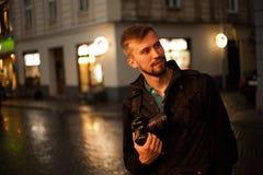 Νέες αρσενικές στάσεις φωτογράφων στην οδό πόλεων το βράδυ Στοκ Εικόνα