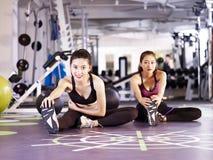 Νέες ασιατικές γυναίκες που τεντώνουν τα πόδια στη γυμναστική στοκ φωτογραφία
