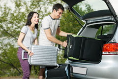 Νέες βαλίτσες φόρτωσης ζευγών στην μπότα αυτοκινήτων Στοκ φωτογραφία με δικαίωμα ελεύθερης χρήσης