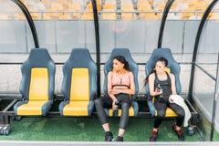 Νέες γυναίκες ικανότητας sportswear που στηρίζεται στα καθίσματα σταδίων Στοκ φωτογραφίες με δικαίωμα ελεύθερης χρήσης