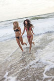 Νέες γυναίκες κοριτσιών στα μπικίνια που τρέχουν στην παραλία Στοκ εικόνες με δικαίωμα ελεύθερης χρήσης
