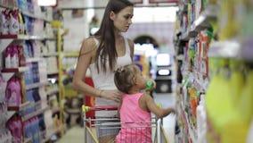 Νέες γυναίκες με λίγη κόρη που επιλέγει τα απορρυπαντικά για το σπίτι στην υπεραγορά απόθεμα βίντεο