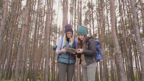 Νέες γυναίκες με το χάρτη που ψάχνουν την κατεύθυνση στο δάσος φιλμ μικρού μήκους