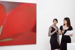 Νέες γυναίκες που εξετάζουν τη ζωγραφική τοίχων στο γκαλερί τέχνης στοκ εικόνες