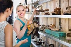 Νέες γυναίκες που επιλέγουν τα παπούτσια Στοκ Εικόνες