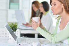 Νέες γυναίκες που εργάζονται με τις ψηφιακές συσκευές στην αρχή στοκ εικόνα με δικαίωμα ελεύθερης χρήσης