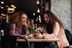 Νέες γυναίκες που κάθονται στον καφέ και που χρησιμοποιούν το τηλέφωνο Στοκ Φωτογραφία