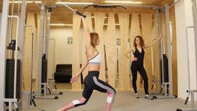 Νέες γυναίκες που κάνουν την ικανότητα στη γυμναστική Μια γυναίκα που κάνει τις ασκήσεις δύναμης σε ετοιμότητα της Μια άλλη γυναί απόθεμα βίντεο