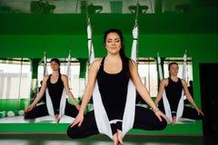 Νέες γυναίκες που κάνουν τις ενάντιες στη βαρύτητα ασκήσεις γιόγκας με μια ομάδα ανθρώπων εκπαιδευτής ικανότητας μυγών aero worko Στοκ εικόνες με δικαίωμα ελεύθερης χρήσης