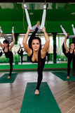 Νέες γυναίκες που κάνουν τις ενάντιες στη βαρύτητα ασκήσεις γιόγκας με μια ομάδα ανθρώπων εκπαιδευτής ικανότητας μυγών aero worko Στοκ Εικόνες