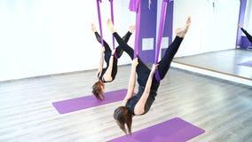 Νέες γυναίκες που κάνουν τις τεντώνοντας ασκήσεις που χρησιμοποιούν τις αιώρες απόθεμα βίντεο