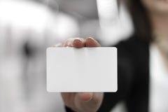 Νέες γυναίκες που κρατούν μια κενή κάρτα στα χέρια Στοκ Φωτογραφία