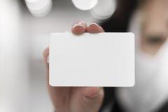 Νέες γυναίκες που κρατούν μια κενή κάρτα στα χέρια Στοκ Εικόνες
