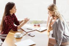 Νέες γυναίκες που μιλούν ενώ διοργανώνοντας τη συνεδρίαση του επιχειρησιακού μεσημεριανού γεύματος στον καφέ Στοκ Εικόνες