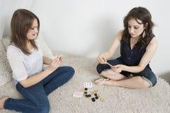Νέες γυναίκες που παίζουν τις κάρτες καθμένος στον καναπέ γουνών Στοκ φωτογραφία με δικαίωμα ελεύθερης χρήσης