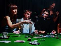 Νέες γυναίκες που ρίχνουν τα τσιπ στον πίνακα παίζοντας τις κάρτες Στοκ εικόνα με δικαίωμα ελεύθερης χρήσης