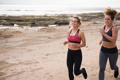 Νέες γυναίκες που τρέχουν στην άμμο από την παραλία Στοκ Εικόνες