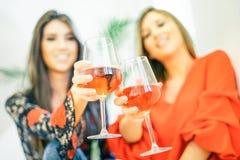Νέες γυναίκες που ψήνουν τα ποτήρια του ροδαλού κρασιού στο σπίτι τους - ευτυχείς αδελφές που απολαμβάνουν το χρόνο τους που πίνε στοκ φωτογραφία