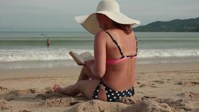 Νέες γυναίκες σε ένα καπέλο μπικινιών και ήλιων που διαβάζει ένα βιβλίο κάνοντας ηλιοθεραπεία στην παραλία απόθεμα βίντεο