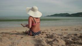 Νέες γυναίκες σε ένα καπέλο μπικινιών και ήλιων που διαβάζει ένα βιβλίο κάνοντας ηλιοθεραπεία στην παραλία φιλμ μικρού μήκους