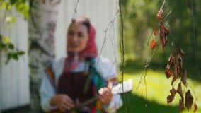 Νέες γυναίκες στα παραδοσιακά ρωσικά ενδύματα που στέκονται κοντά σε ένα ξύλινο balalaika κτηρίου και παιχνιδιού απόθεμα βίντεο