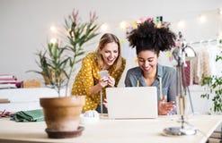 Νέες δημιουργικές γυναίκες με το lap-top στο στούντιο, επιχείρηση ξεκινήματος Στοκ εικόνα με δικαίωμα ελεύθερης χρήσης